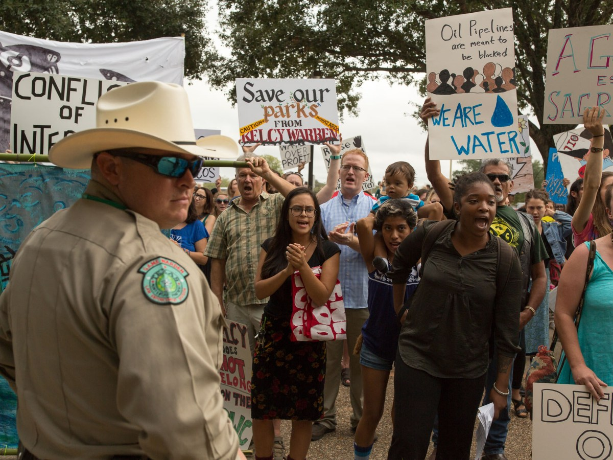 Game Warden Cody Buckalook looks backwards as protestors come within feet of the front entrance to the Texas Parks and Wildlife headquarters demanding for Kelcy Warren to step down from the board.