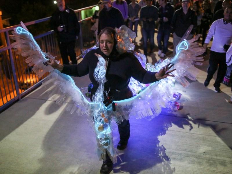 Local artist Margaret Craig walks her installation opens her arms as she walks her installation / performance piece titled 'Albatross' on the Hays Street Bridge.