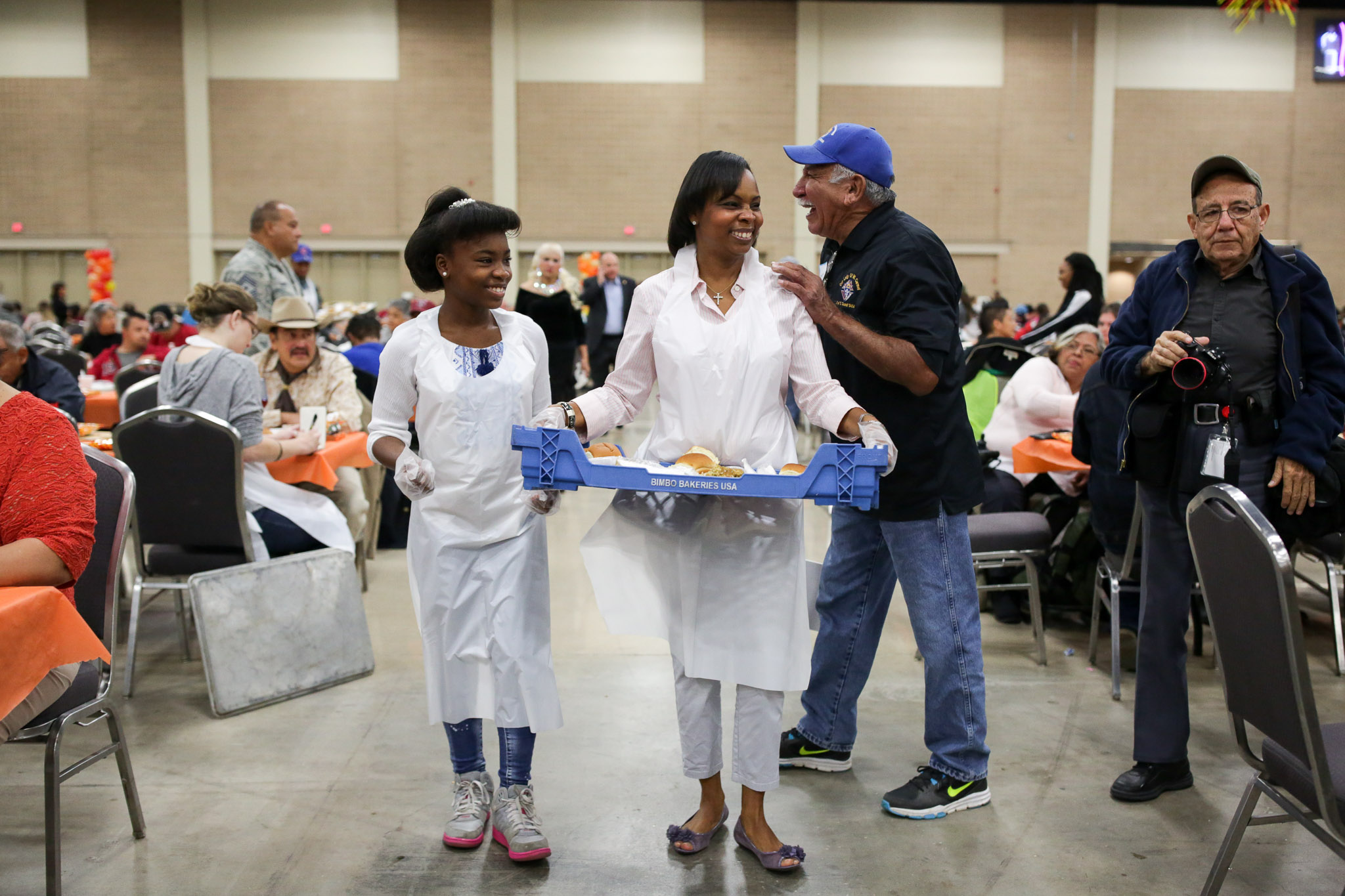 Mayor Ivy Taylor and her daughter Morgan smile as they are greeted by patrons of the Raul Jimenez Thanksgiving Dinner.