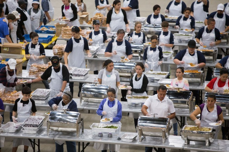 Volunteers form an assembly line portioning food to individual plates to be served.