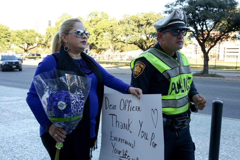Concerned citizen Lucy Aldaba is escorted by a San Antonio Police Officer to lay down a bouquet of flowers along with a sign in remembrance of the fallen officer.
