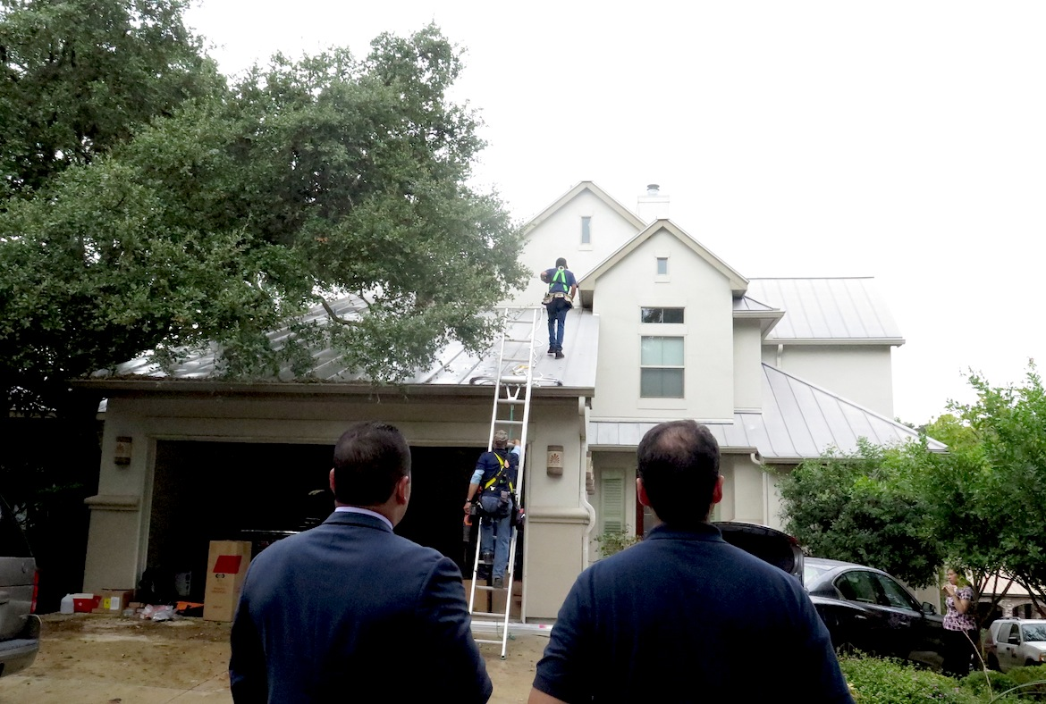 State Sen. José Menéndez (D-26) and Ben Rodriguez (left) watch from the street as a crew from Advanced Solar install solar panels on Mendéndez's roof.