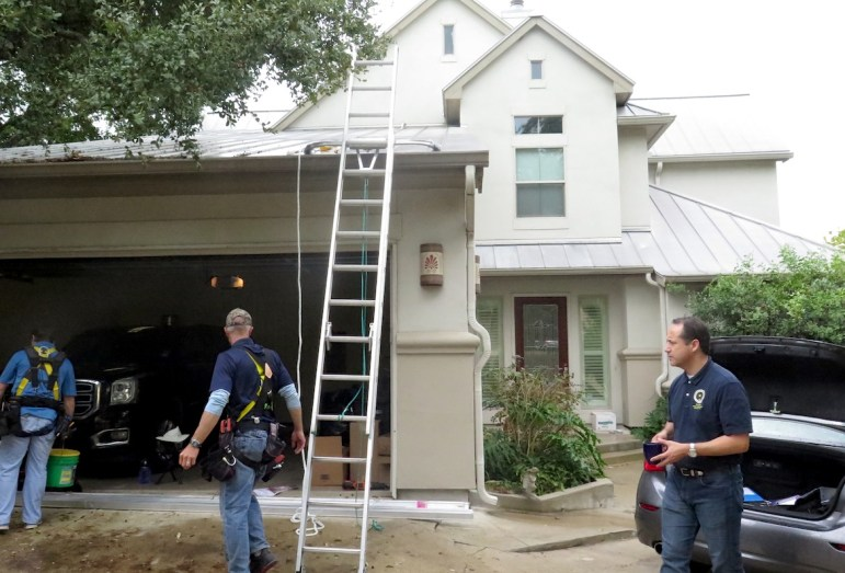 Workers prepare to install solar panels at the home of State Sen. José Menéndez (right).