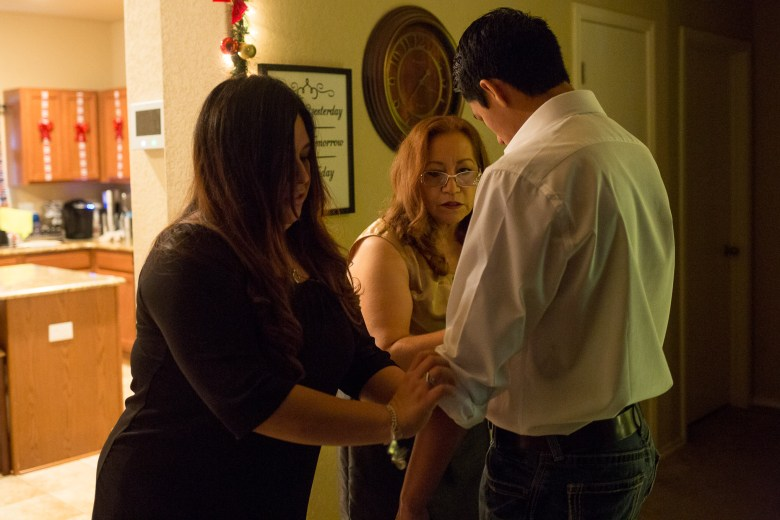 Gina García and her mother Georgina García fold up the sleeves of her oldest is Nomar García Ybarra's shirt before the graduation.