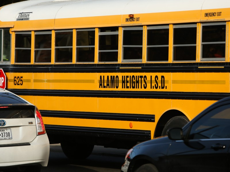 An Alamo Heights I.S.D. bus passes Alamo Heights High School on Broadway.