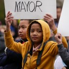 A young boy raises a sign supporting Ron Nirenberg for mayor.