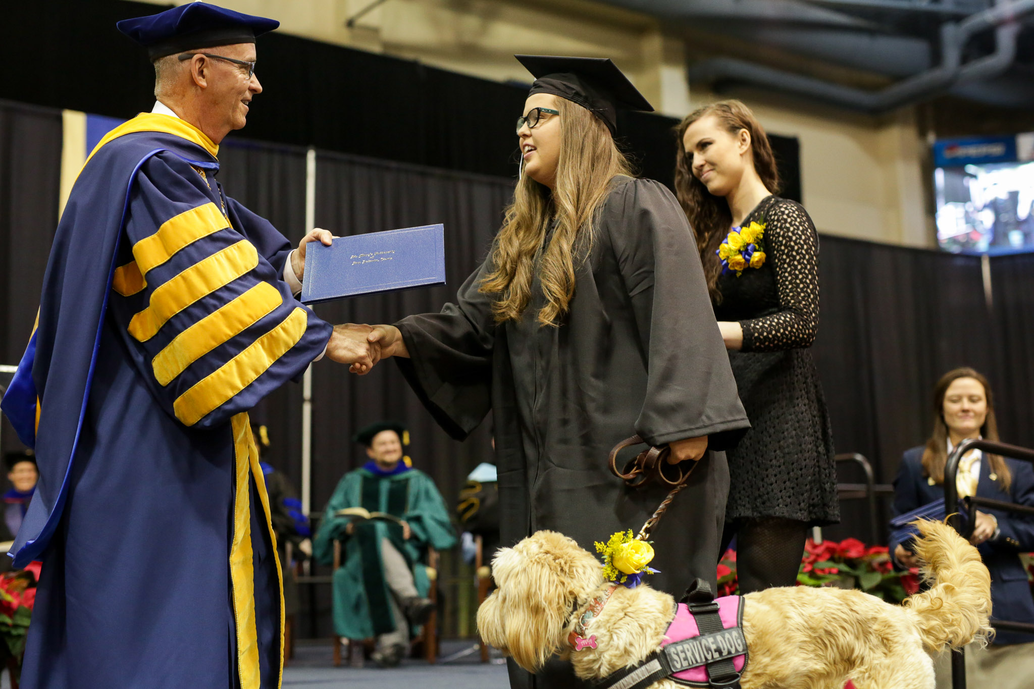 Mikayla Bass accepts her diploma from the President of St. Mary's University, Thomas Mengler.