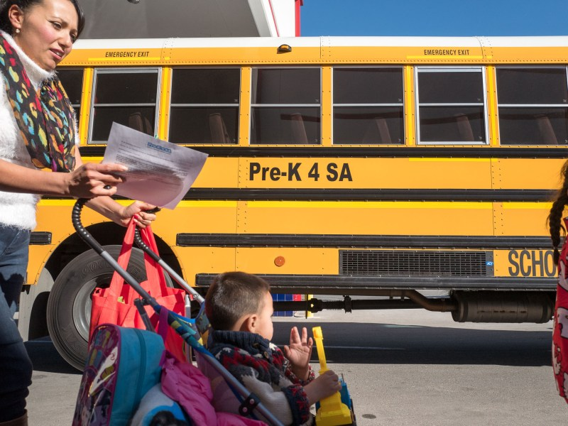 Parents walk their children by Pre-K 4 SA school bus on their way home for the holidays.