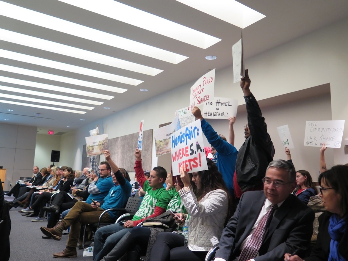 Hemisfair advocates and protesters hold up signs during the the final Parks and Recreation Bond Committee meeting. Photo by Iris Dimmick.