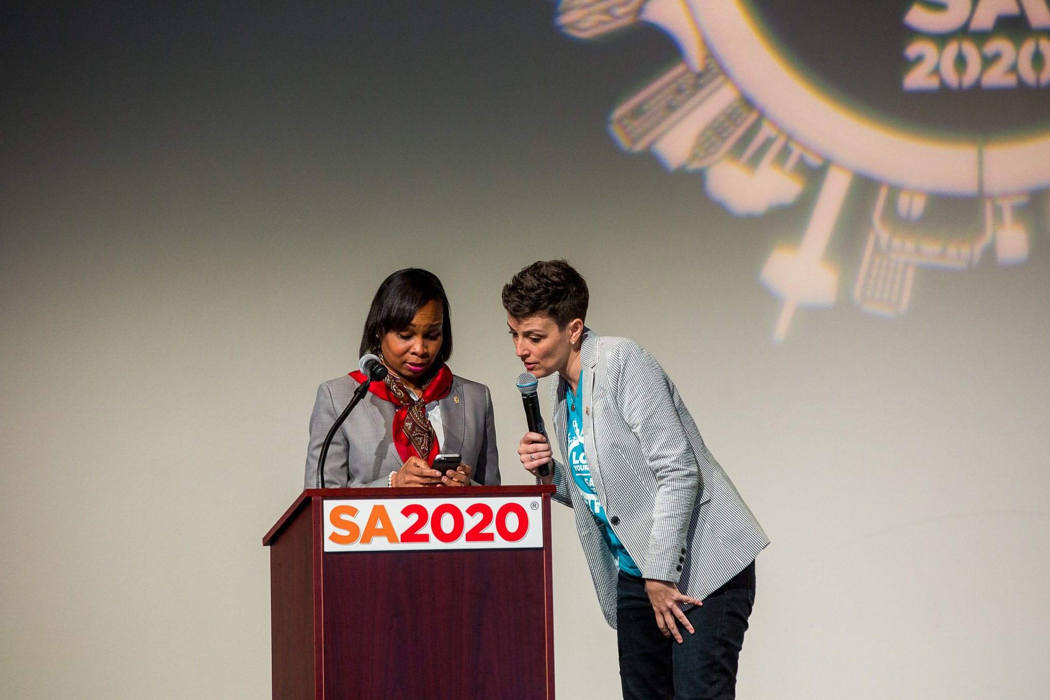 SA2020 President and CEO Molly Cox helps Mayor Ivy Taylor participate in a cell phone survey about the actions attendees will take to help SA2020's mission.
