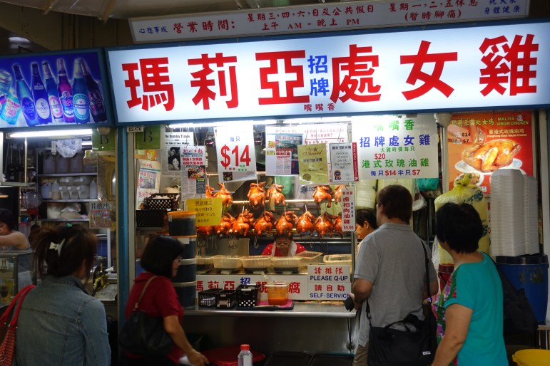 Chicken rice plate coming up at a Singapore market stall.
