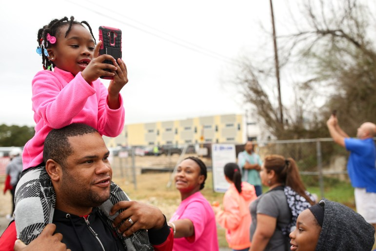 Trinity, 5, uses her mothers phone to take a photograph from her vantage point atop of her father, Charles Trammell
