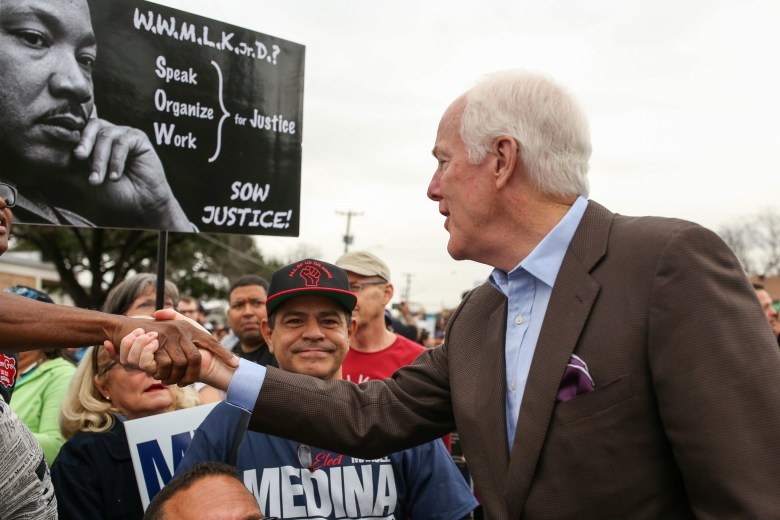 U.S. Sen. John Cornyn (R-Texas) shakes hands with fellow participants at the start of the march.