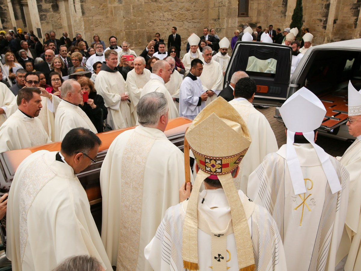 Members of the clergy pay respects to the late Archbishop Flores as the casket is slowly walked to the hearse.