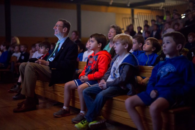 Head of School John Webster watches a clip from the film 'Rocky,' which ties into his theme of overcoming challenges, during his daily chapel session.