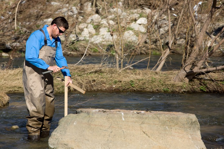 Senior Aquatic Biologist Shaun Donovan drives wooden stakes into the riverbed marking location parameters for the test site.