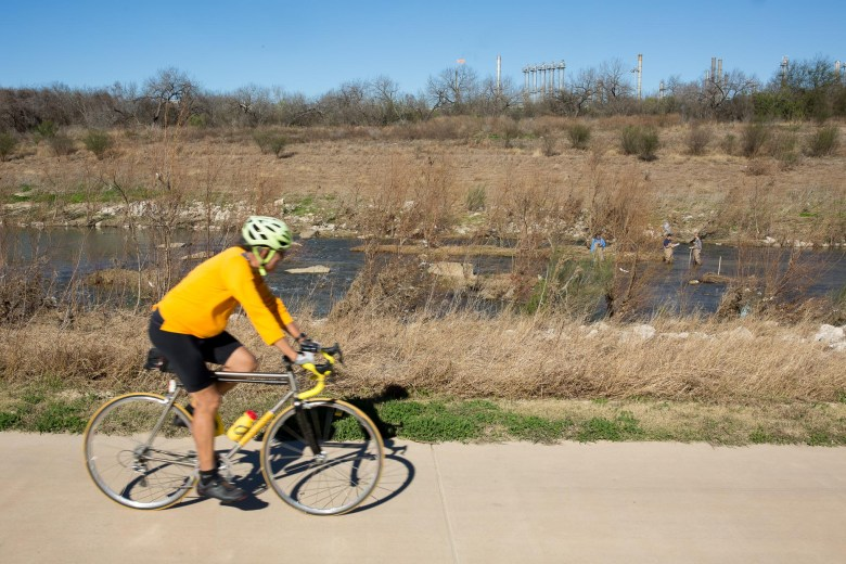 A cyclist passes by along the San Antonio Mission Reach as SARA Aquatic Biologists conduct studies on the mussel species in the San Antonio River as a fuel refinery lingers in the background.