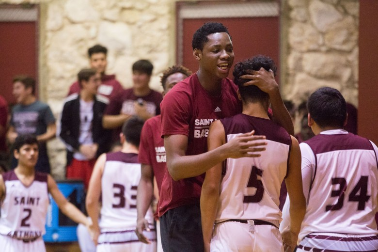 St. Anthony sophomore and the nation's No. 2 recruiting prospect Charles Bassey congratulates freshman Jordan Persad during a game against KIPP Monday the 23rd.