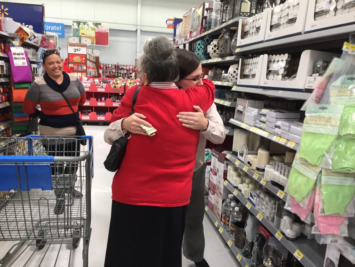 Jefferson Bank employee Charity Curbo hugs a customer at a Wal-Mart shopping center as she is given cash to help with holiday shopping.