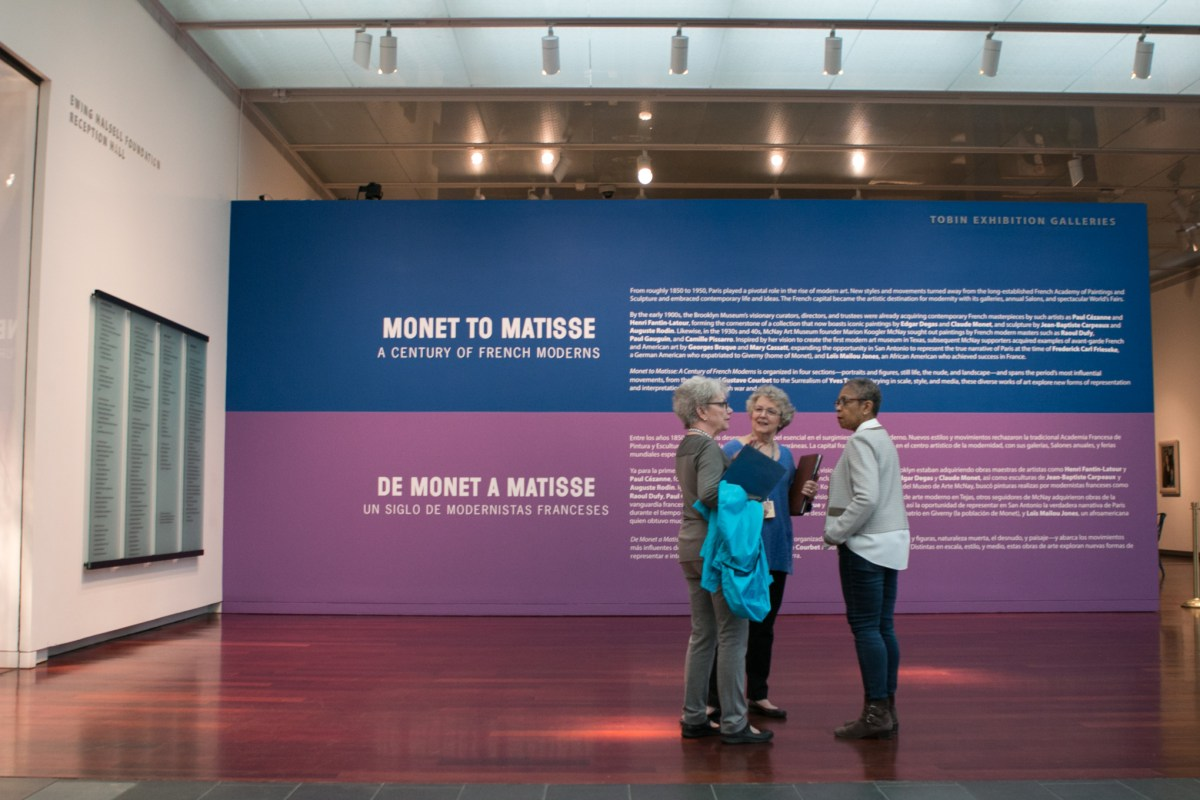"""From left, Raye Foster, Anne Beverly, and Linda Smith stand in front of the entrance to the exhibit """"Monet to Matisse: A Century of French Moderns."""""""