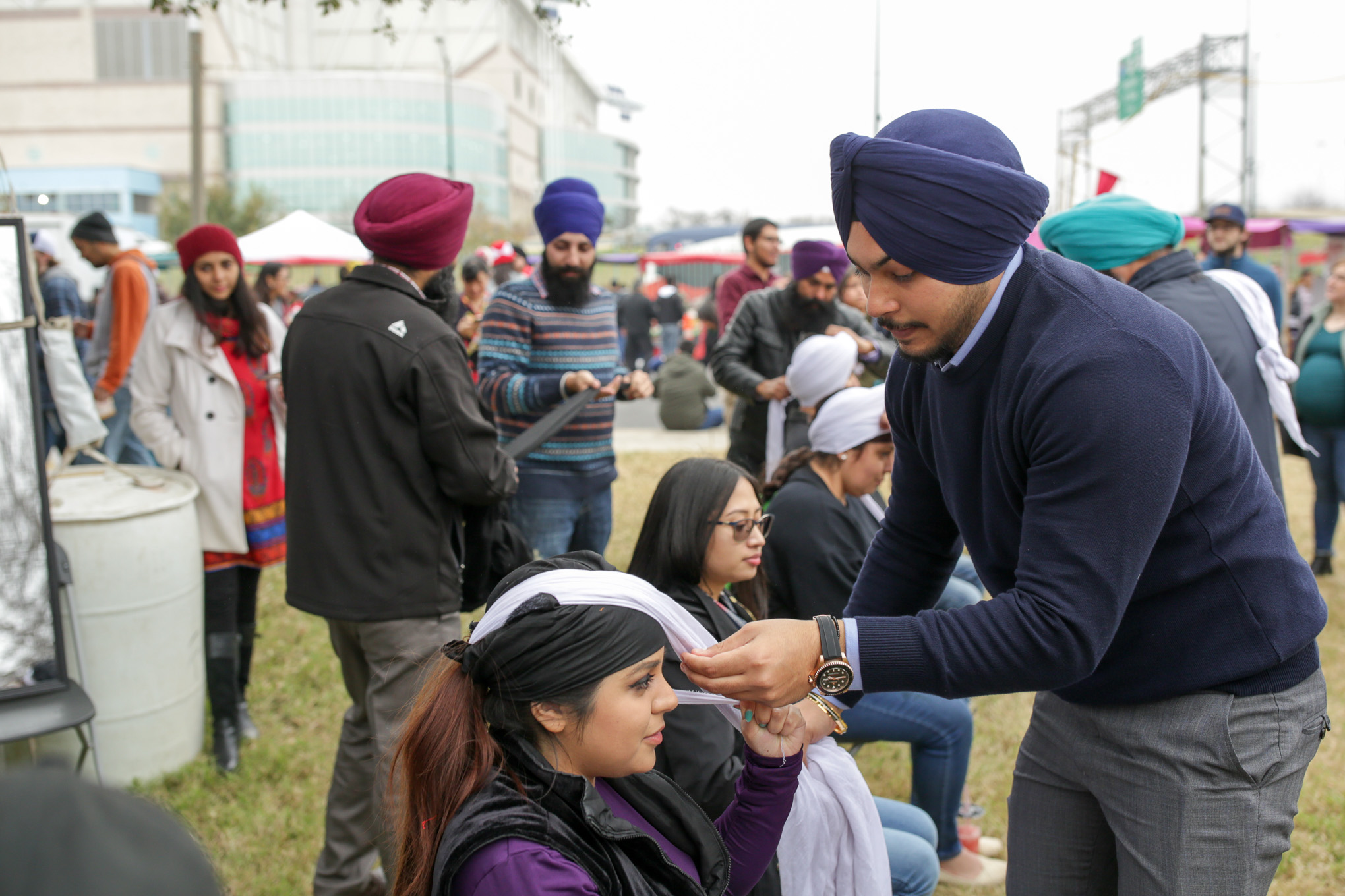 Amandeep (right) ties a turban around an attendee at the Sikh Dharamsal booth. The turbans were given and clothed at no charge and over two hundred were claimed.