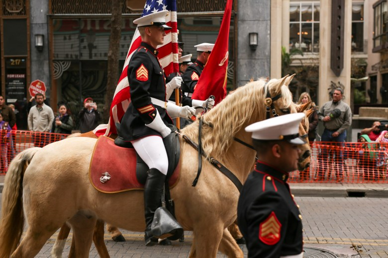 Members of the United States Marine Corps on horseback continue down the parade route.