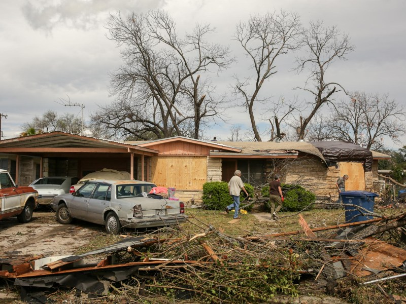 Neighbors survey the damage done to a home off Linda Drive.