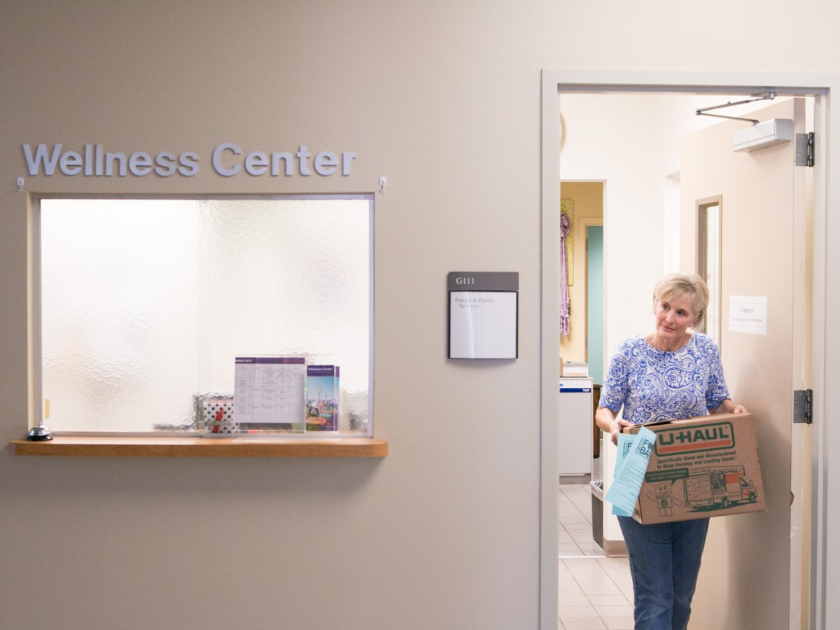 SA Cancer Council volunteer Carla Bergner carries a box of food provided by the CTRC Food Pantry at the Wellness Center.