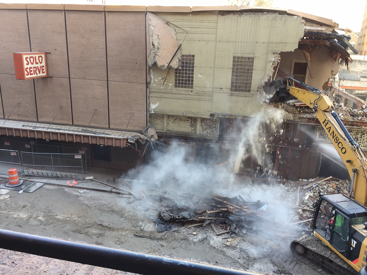 Crews demolish the historic Solo Serve building.