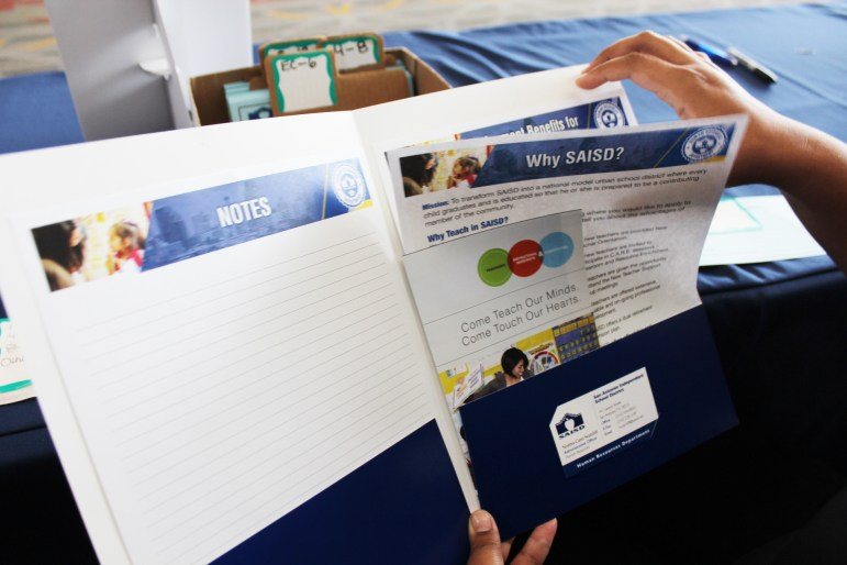 A teacher sifts through an information folder at the SAISD Master Teacher Job Fair.