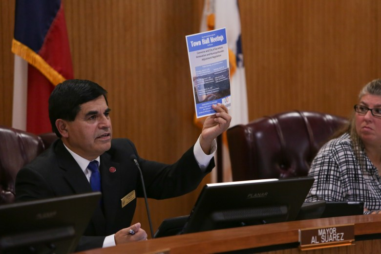 Converse Mayor Al Suarez holds up a sign indicating the upcoming town hall meetings on the proposed annexation plan.
