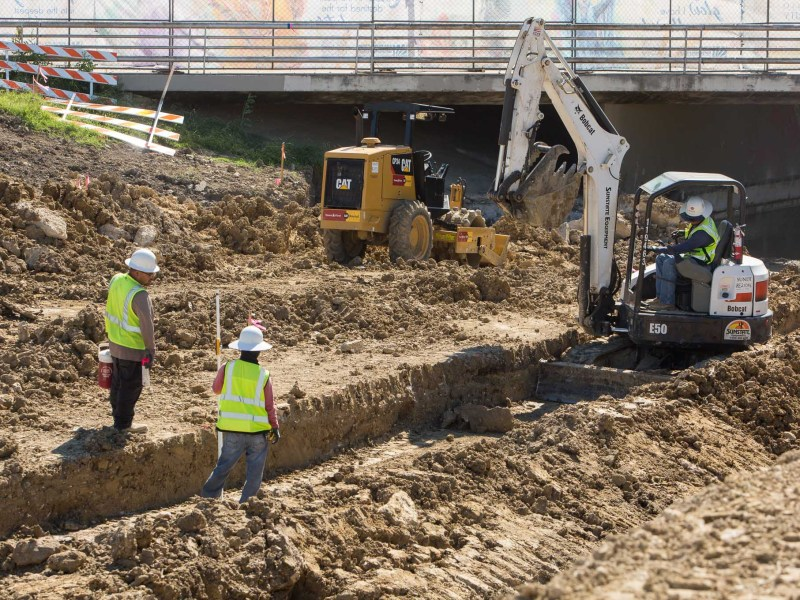 Workers trench the San Pedro Creek widening the area resulting in a four inch deep flow upon project completion.