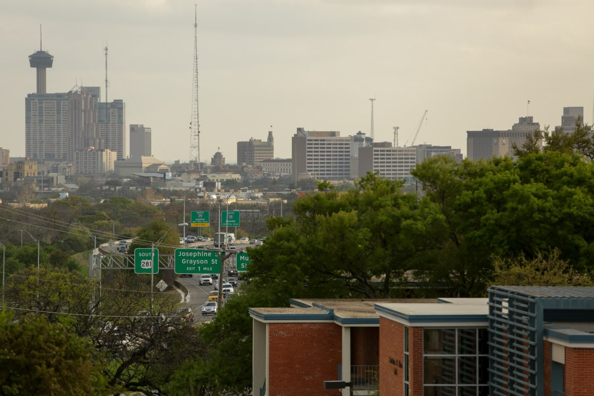 The skyline of San Antonio is visible through the trees on the outskirts of downtown.