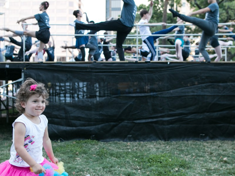 Grace, 3, watches the ballerinas while wearing a tutu of her own at Ballet in the Park.