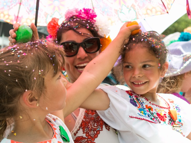London, 5, (left) and Giuliana, 7, (right) crack cascarones on each other's heads as Valerie Johnson encourages them at the Battle of Flowers Parade.