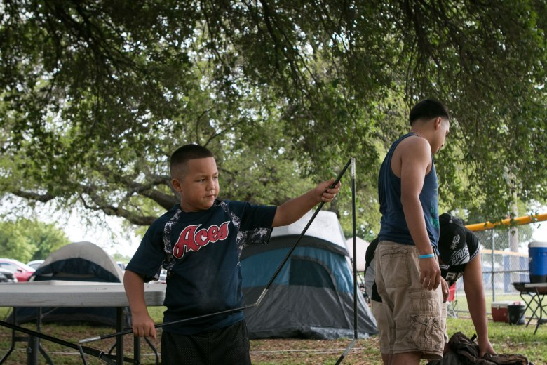 Gabriel, 6, (left) helps his family set up their tent during Easter weekend in Brackenridge Park.