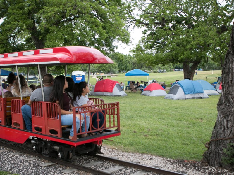 Families look at the tents set up for Easter weekend from the train in Brackenridge Park.