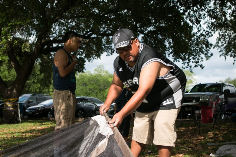 (From left) Victor Roman II and his father Victor Roman set up their tent during Easter weekend in Brackenridge Park.