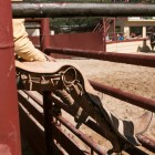A charro sits on the fence to watch the performance at A Day in Old Mexico & Charreada.