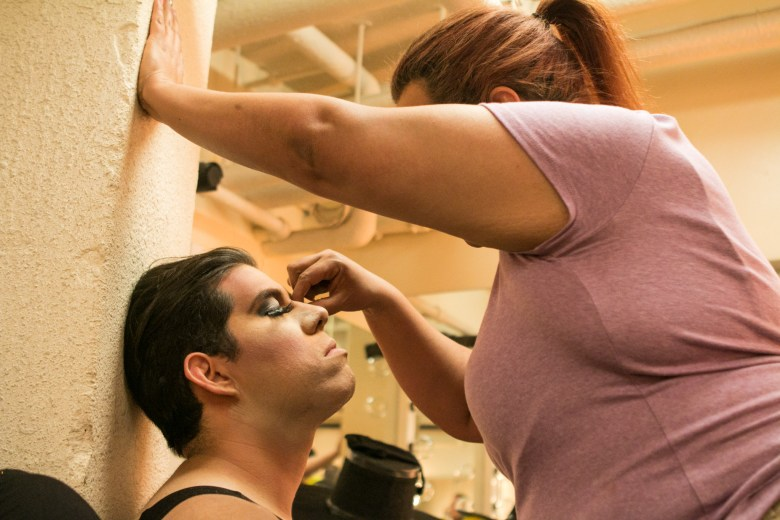 Actor Josie Dulzuro is assisted with his makeup before performing in Cornyation at Charline McCombs Empire Theatre during Fiesta.