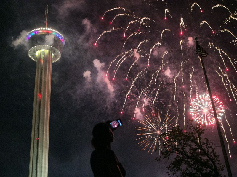 A woman records the fireworks exploding over Hemisfair Park during Fiesta Fiesta.