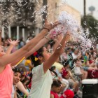 (From left) Gaby, 11, and Audrey, 10, throw confetti into the air during the Fiesta Flambeau Parade.
