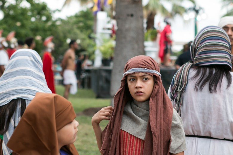 A young child actress waits to begin the Passion of Christ Procession.