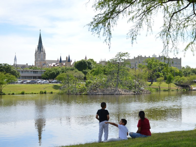 Family sitting on the banks of Elmendorf Lake with Our Lady of the Lake University in the background.