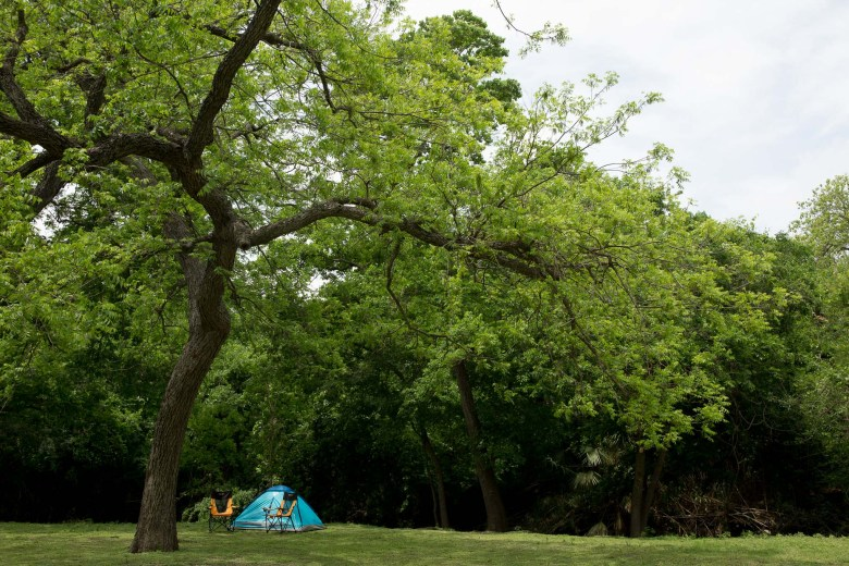 A small tent is pitched near the banks of the San Antonio River at Brackenridge Park.