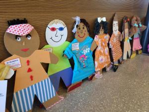 "Cardboard kids created by City of San Antonio Head Start program employees ""line up"" against a wall."