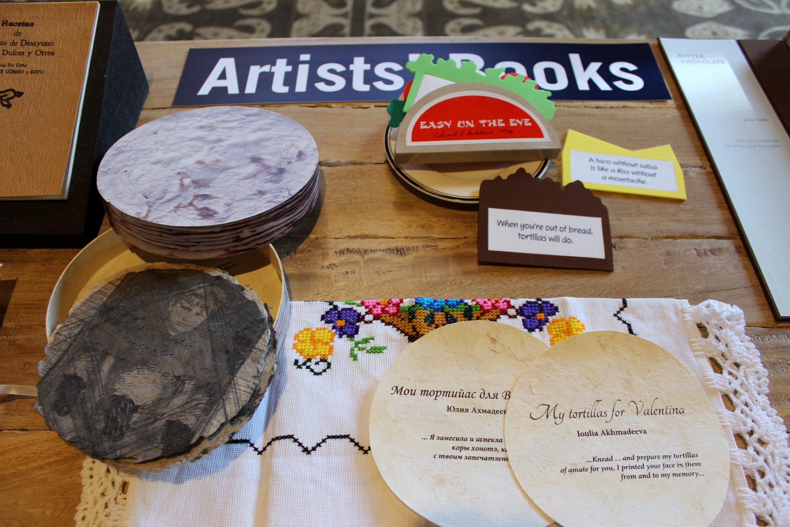 A book (in Russian and English) shaped like tortillas and a book crafted like a taco are part of the special collection.