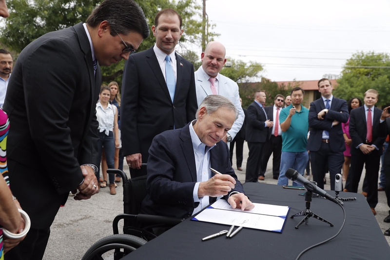 As lawmakers and Lyft and Uber drivers look on, Gov. Abbott signs House Bill 100, which creates statewide regulations for ride-hailing companies, in Austin on May 29, 2017.