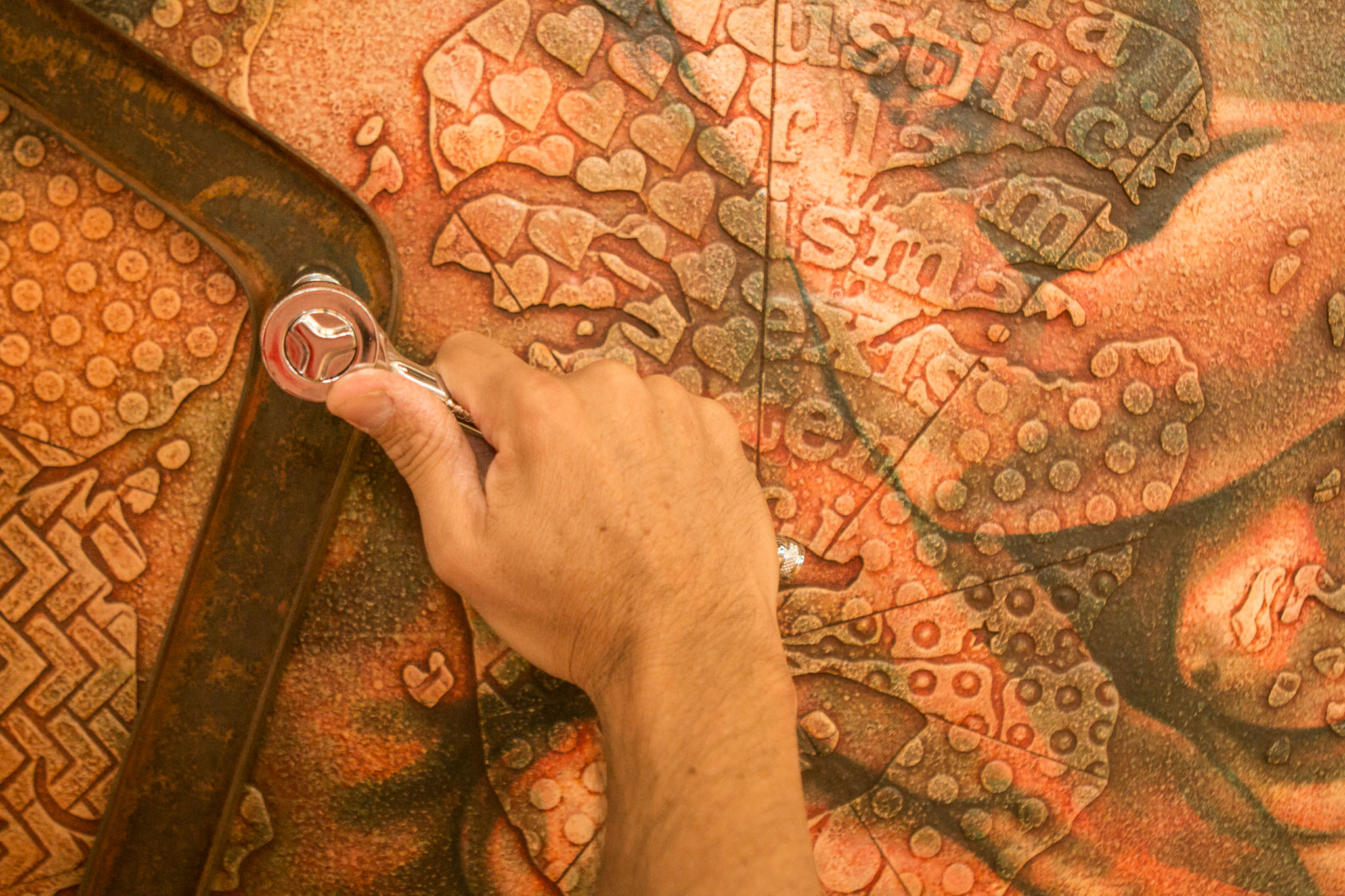 Artist Adrian Rumbaut makes adjustments on a work before the Cuerpo Cubano / Cuban Body show at Bihl Haus Arts.