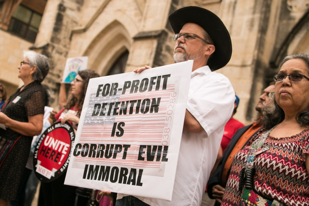 Rev. John Feagins holds a sign in protest of Senate Bill 4 in front of San Fernando Cathedral.